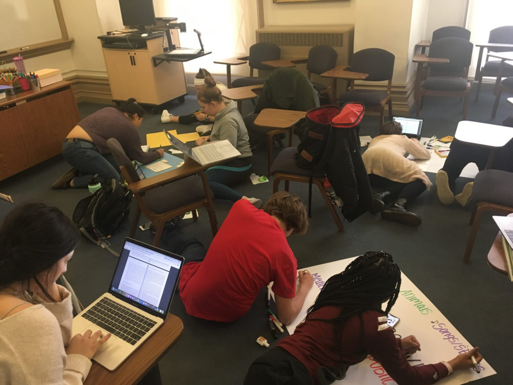 students sitting on the floor, working on colorful projects