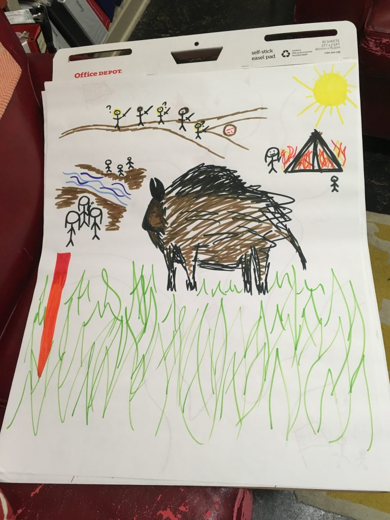 A drawing of a buffalo, a red-tipped stick, and stick figures traveling along a road