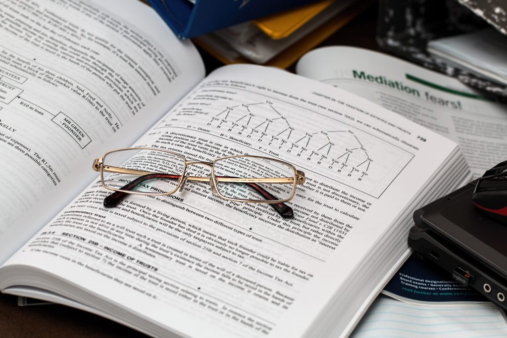 An open accounting book with a pair of glasses on top of it.
