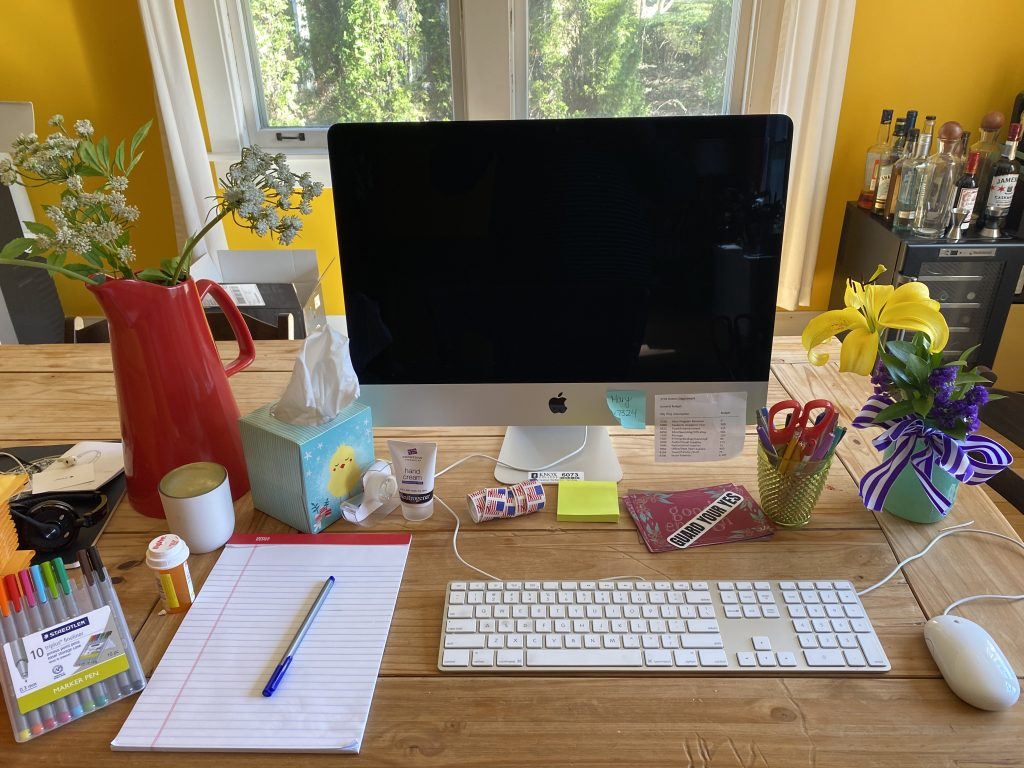 A photo of a computer on a dining room table, with a notepad beside it, and two vases of flowers. There is a window behind the computer.
