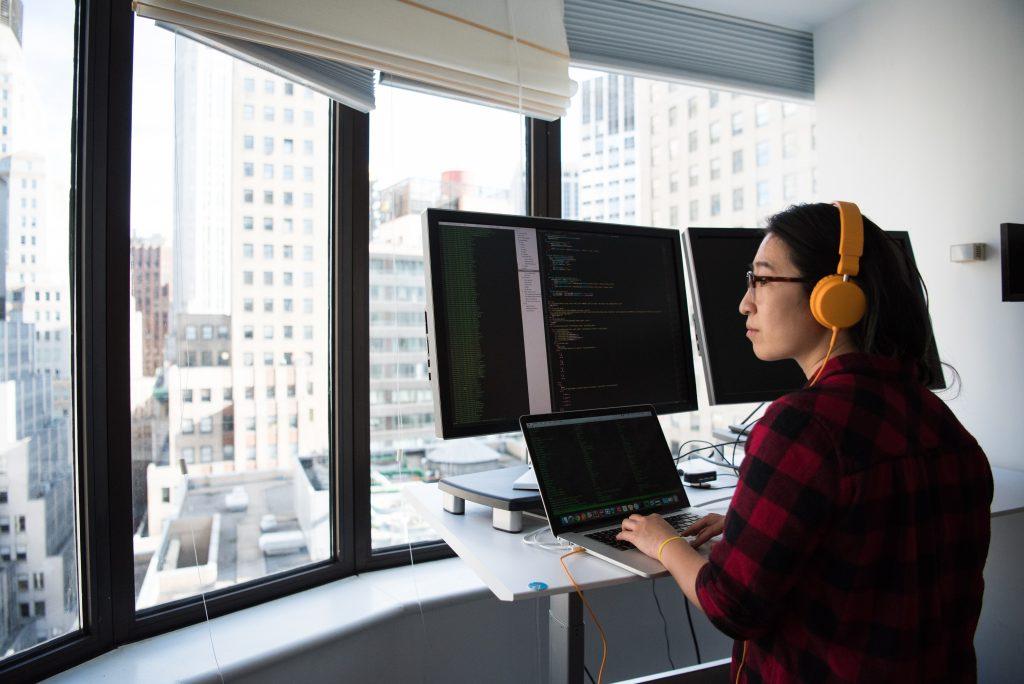A woman at a computer, thinking