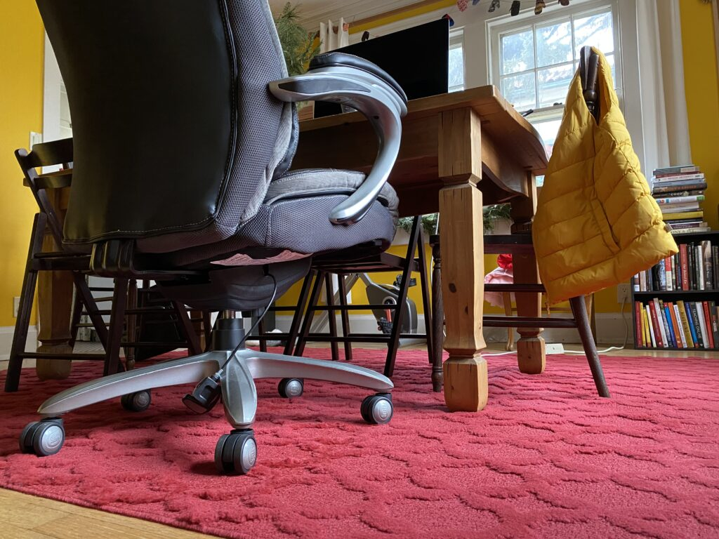 Taken from the floor, this photo shows a red rug, a table, an office chair, a bookcase full of books, and the yellow walls of a room