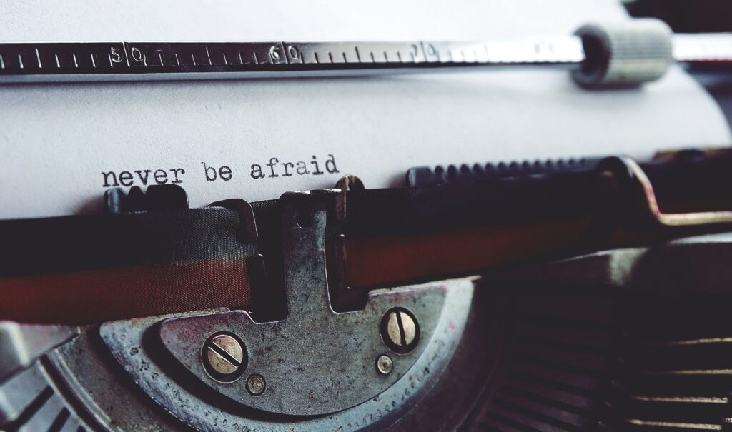 """An old-fashioned typewriter with a piece of paper in it. The words """"Never be afraid"""" have been typed on the paper."""