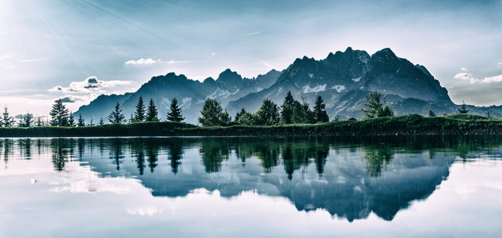 A photograph of mountains reflected in a lake.
